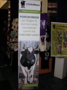 """Pannello di Vita da Cani relativo al progetto Porcikomodi, con immagine di una mucca e la scritta: """"Porcikomodi, un rifugio in cui non sono considerati carne ma individui unici"""""""