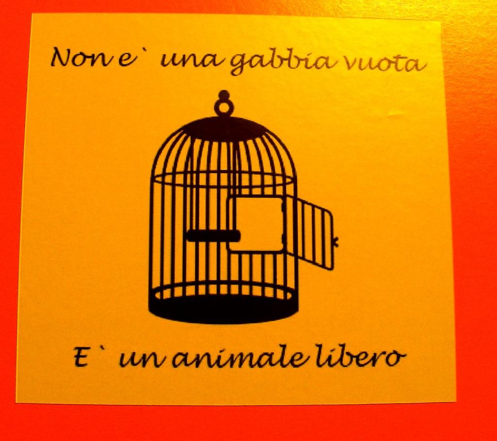 """Foto di un adesivo che rappresenta una gabbia vuota e reca la scritta: """"Non è una gabbia vuoa, è una animale libero""""."""